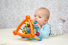 Blue eyes baby biting a toy Royalty Free Stock Photography