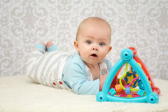 Blue eyes baby playing with toy. Blue eyes baby girl lying on belly on soft surface , playing with colourful toy and looking at the camera Royalty Free Stock Images