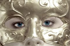 Blue eyes behind the mask Stock Images