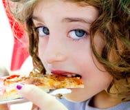 Blue eyes child girl eating pizza slice. Hungry stock photo