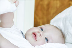 Blue eyes child is laying on bed Stock Photo