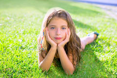 Blue eyes children girl on garden grass. Blue eyes children girl relaxed on the garden grass lying with hands in face royalty free stock images