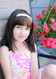 Blue eyes dark hair. A very cute little girl with blue eyes and dark hair sitting by pink flowers. Shallow depth of field Royalty Free Stock Image