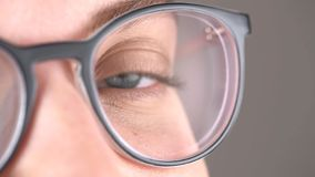 Blue eyes of the girl in glasses close-up, glasses for vision correction, beautiful stylish frame.  stock footage