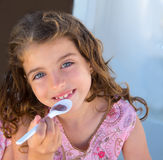Blue eyes kid girl eating breakfast with spoon. Portrait stock images