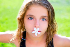 Blue eyes kid girl with jasmine flower in mouth. Blue eyes children girl with jasmine flower in mouth at garden grass stock photo