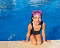 Blue eyes kid girl on knees on blue pool poolside. With snorkel pink glasses royalty free stock photography