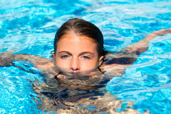 Blue eyes kid girl at the pool face in water. Beautiful blue eyes kid girl at the pool with face in water surface royalty free stock photography