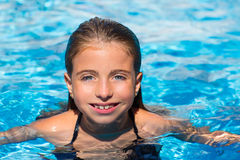 Blue eyes kid girl at the pool in summer vacation. Beautiful blue eyes kid girl at the pool with face in water surface royalty free stock photography