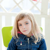 Blue eyes kid girl portrait outdoor sit in chair Stock Photos