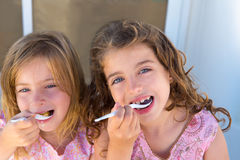Blue eyes kids sister girl eating breakfast. With spoon royalty free stock photo