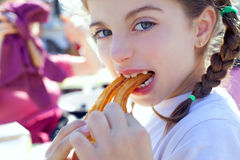Blue eyes little girl eating churros smiling Royalty Free Stock Image