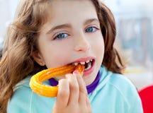 Blue eyes little girl eating fried crullers Stock Image