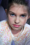 Blue eyes and pearls. A very cute little girl with blue eyes and dark hair wearing pearls, beads and makeup. Shallow depth of field Royalty Free Stock Photo