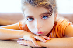 Blue eyes sad children girl crossed arms. On table Stock Photography