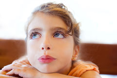Blue eyes sad children girl crossed arms. On table Royalty Free Stock Photos