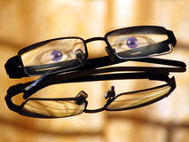 Blue eyes staring, glasses, spectacles. A pair of paranormal looking blue eyes staring through empty glasses or spectacles kept on a reflecting glass surface Stock Images