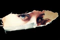 Blue eyes of young woman peeping through a hole. Closeup Stock Photos