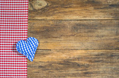 Blue fabric heart and red checkered fabric on rustic wood. Background for Oktoberfest with blue heart and red checkered fabric on rustic wooden board with copy Royalty Free Stock Photos