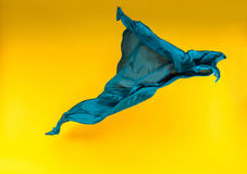 Blue fabric over yellow background. Abstract pieces of fabric flying, high-speed studio shot Stock Images