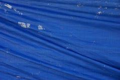 Blue fabric texture from crumpled worn tarp covering. Blue background of fabric from crumpled shabby tarp covering stock photo