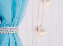Blue fabric on a white wooden background in selective focus. The curtain is decorated with white pearls. In the background, electr. Ic lamps are visible in the Stock Photo