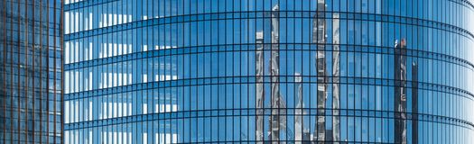 Blue facade of an office building with glass windows stock image