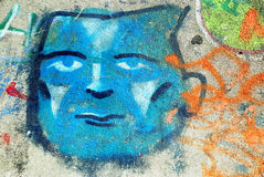 Blue Face Graffiti. A photograph of a spray painted graffiti face Stock Images