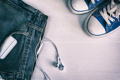 Blue faded jeans and blue sneakers on a white wooden background Royalty Free Stock Image