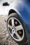 Blue Family Car. Steering front wheel of a blue shiny family car. Tire and rim stock photo