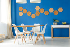 Blue family dining space design. Idea with white and wooden table, chairs and eco cork wall accessories royalty free stock photos