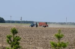 Blue farm tractor fertilize the field. At spring stock photography