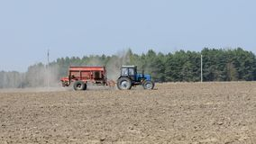 Blue farm tractor fertilize the field. At spring royalty free stock images