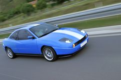 Blue fast racing car on the highway Stock Image