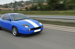 Blue fast sport car on hiway. Blue sport racing car drive fast on highway captured with long exposure Royalty Free Stock Image