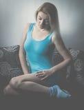 Blue feelings. Blond woman in blue dress sitting on bed stock image