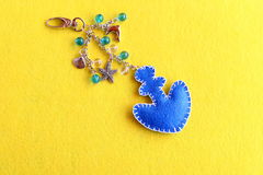Blue felt anchor keychain with beads  on a yellow background. Sewing technique for children, women, beginners. Step Royalty Free Stock Photography
