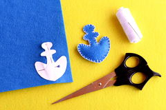 Blue felt anchor is sewn with white thread, needle, paper pattern pinned on a flat piece of blue felt, scissors. Step Stock Photography