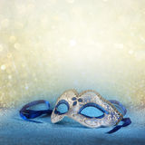 Blue female carnival mask and glitter background. with glitter overlay Royalty Free Stock Photo