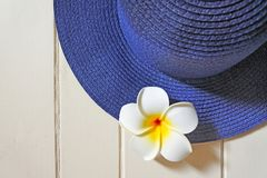 Blue female hat with white Plumeria flower on a wooden surface. Flat lay of Blue female hat with white Plumeria flower on a wooden surface. Travel, vacation Royalty Free Stock Photography