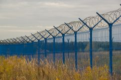 Blue fence with barbed wire in the field royalty free stock image