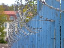 Blue fence with barbed wite spiral Stock Images