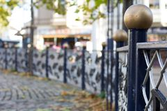 Blue fence with gold ball on top of post. Metal fence with gold balls on top of blue posts found in Triangle Park Teignmouth England Royalty Free Stock Photos