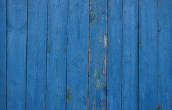 Blue fence of wooden planks. Old blue fence made of many wooden planks with peeled paint and scratches as a background royalty free stock photo
