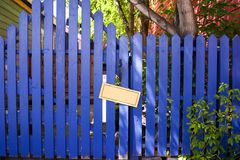 Blue Fenced Door with a Blank Sign Royalty Free Stock Images