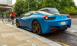 Blue Ferrari 458 parked in street in London. With cyclist taking mobile phone photograph Stock Photos