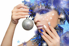Blue festive manicure and makeup. Blue festive manicure with colorful nail Polish and silver Christmas ball in the hand stock photography