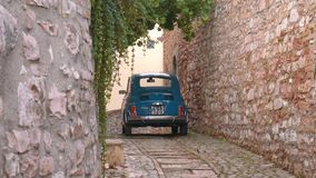 Blue Fiat 500 car parked in a medieval alley in Italy.  stock video footage