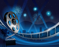 Blue film reel movie background in front of hollywood city at night. Vector illustration of a film stripe reel on shiny blue movie background stock illustration