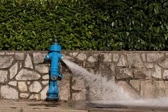 Blue fire hydrant. From which water flows, photographed horizontal Stock Images